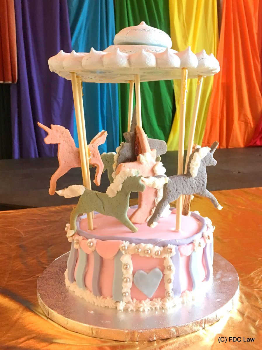 pink, lavender and grey cake in the shape of a fairground carousel, against a rainbow flag backdrop