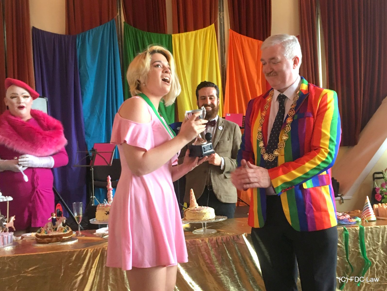 girl in pink dress accepting prize cup from a man wearing a rainbow jacket
