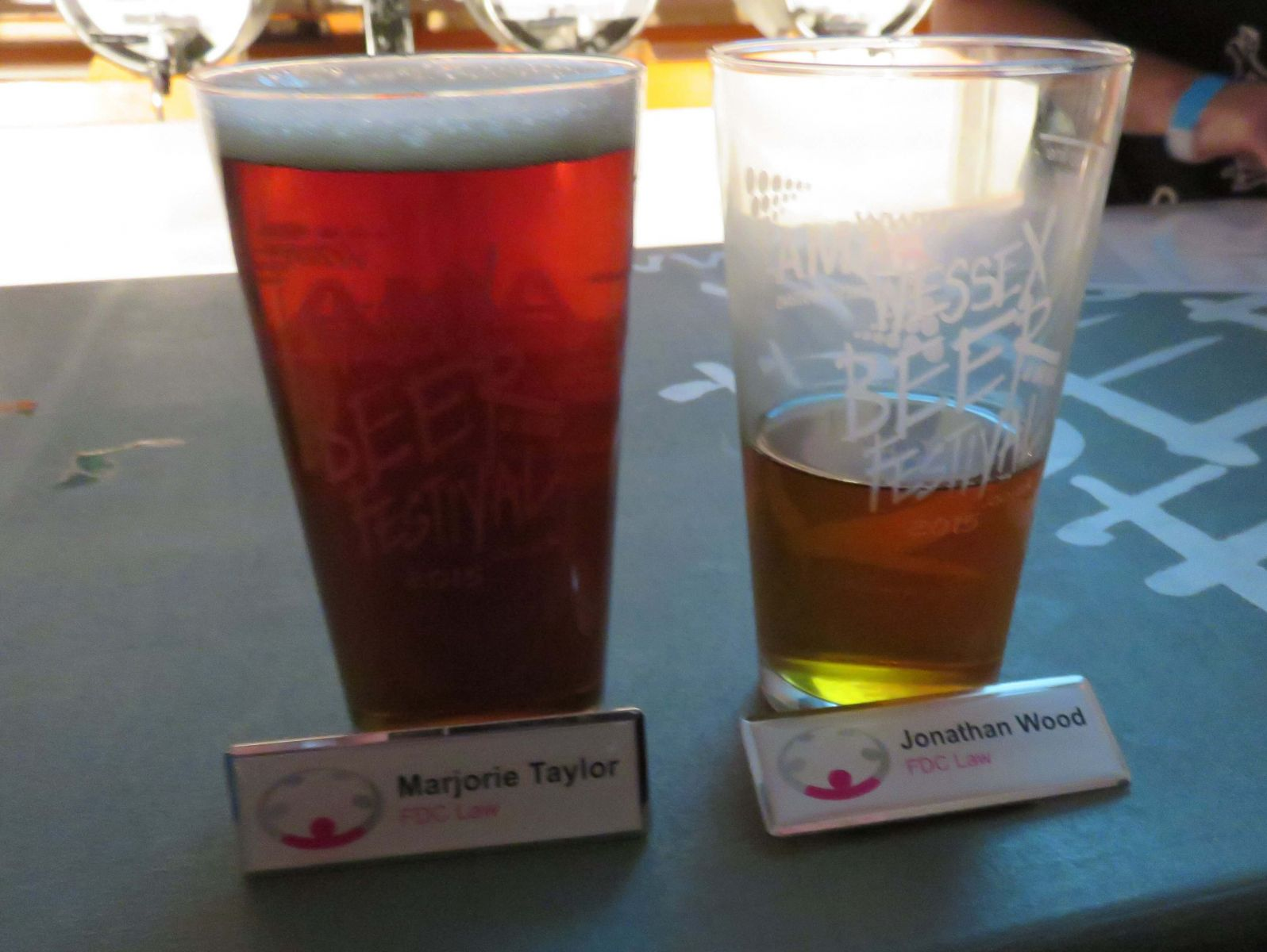 two beer glasses, one full, one half empty, plus 2 name badges