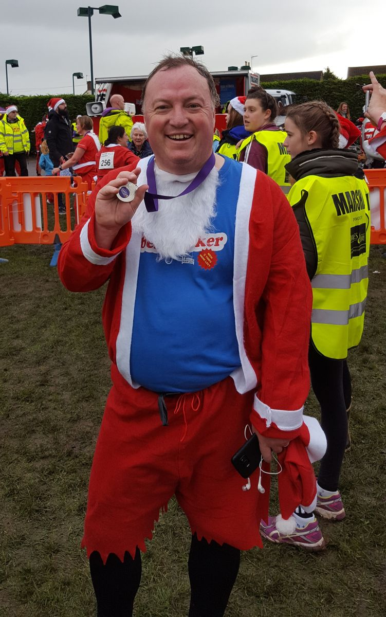 Simon Twose dressed as Santa holding medal